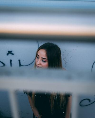 Young woman seen through window