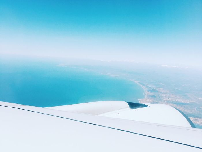 Cropped Image Of Airplane Flying Over Sea Against Blue Sky