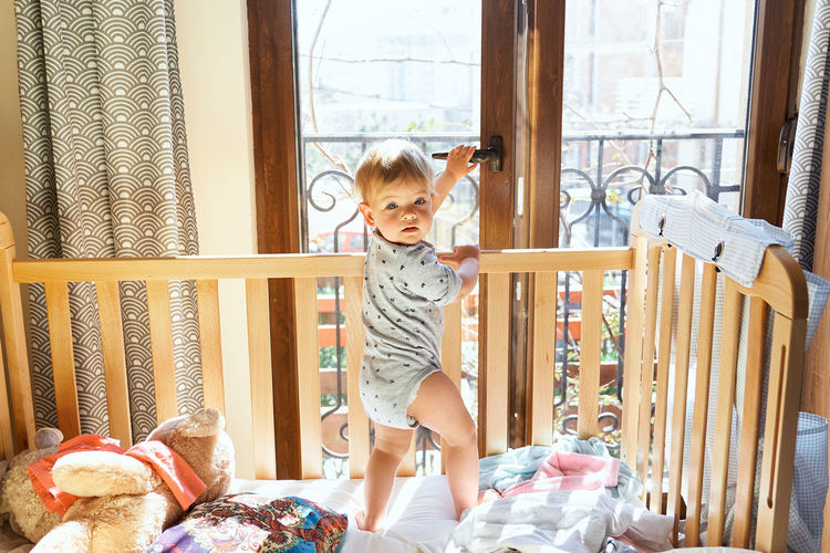Boy playing on window at home