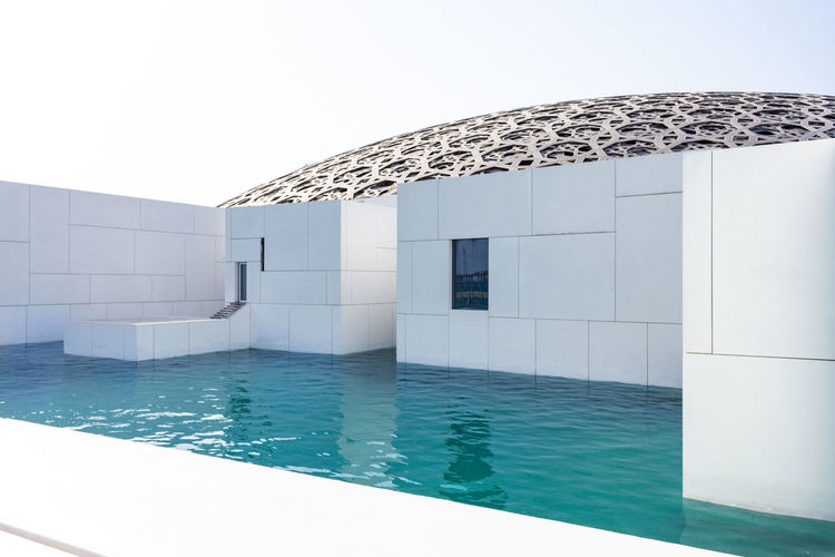 View of swimming pool by building against clear sky