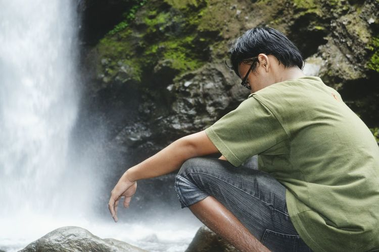 Man crouching against waterfall