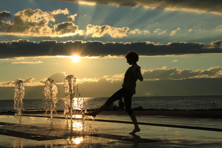 Side view of young woman playing with fountain at beach