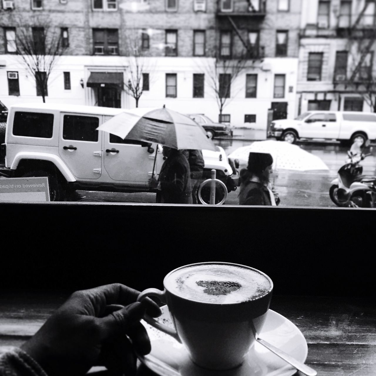 Hand Holding Cappuccino Against Vehicle On Road
