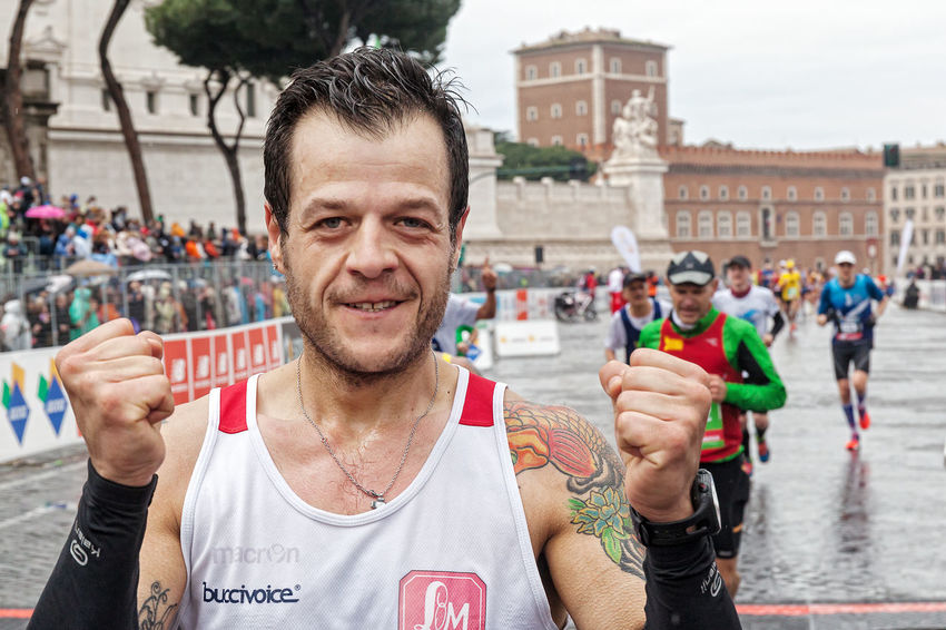 Rome, Italy - March 22, 2015: A participant in the Rome Marathon clenches his fists in victory after arrival at the finish line. Athlete Atletic City City Life Competition Day Force Fun Happiness Italy Man Marathon Outdoors Portrait Rain Rome Runners Running Street Running Strong Water