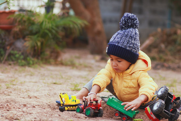 Cute boy playing with toys while sitting on land