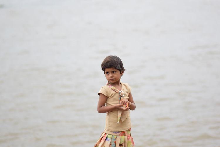 Portrait of cute boy standing in water