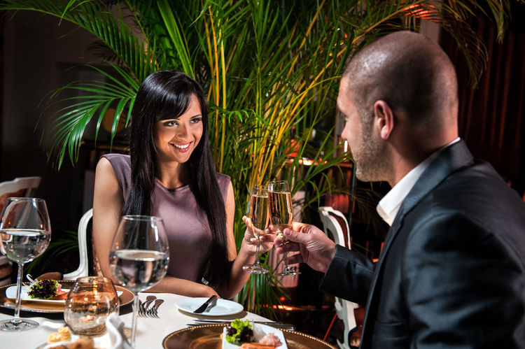 Beautiful couple at restaurant on romantic date Alcohol Attractive Beautiful Brunette Caucasian Celebration Champagne Cheers Couple - Relationship Date Dinner Flirt Handsome Interior Love Man Restaurant Romance Romantic Romantic Dinner Sitting Smiling St Valentine's Day Table Setting Woman