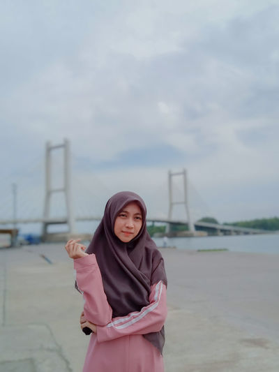 Young woman wearing hijab standing against bridge