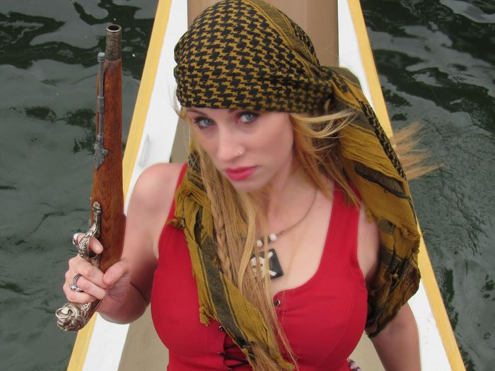 Portrait Of Female Pirate Holding Gun On Boat In Sea