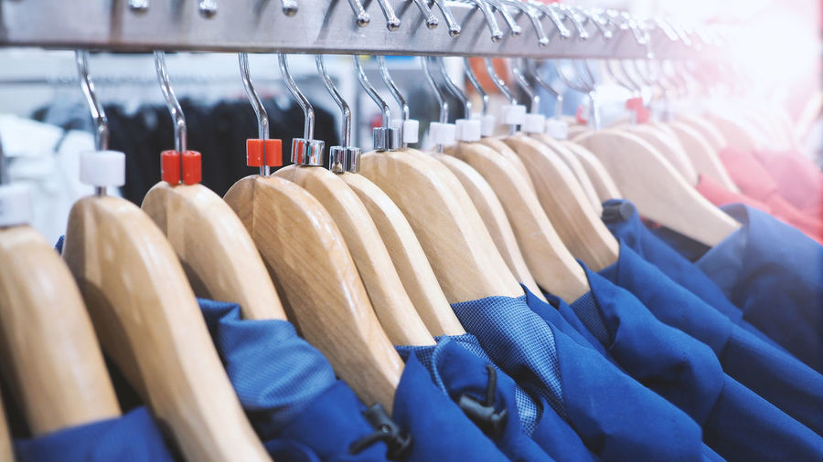 Close-Up Of Blue Clothes Hanging On Rack In Store For Sale