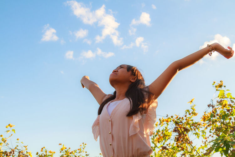 Low angle view of young girl with arms outstretched standing against sky