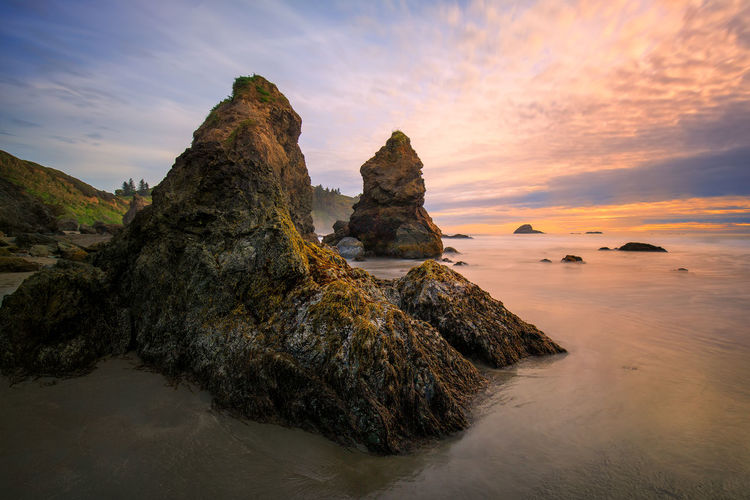 Rock formation on beach against sky during sunset