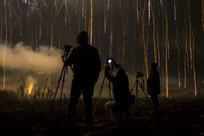 Silhouette men photographing firework display at night