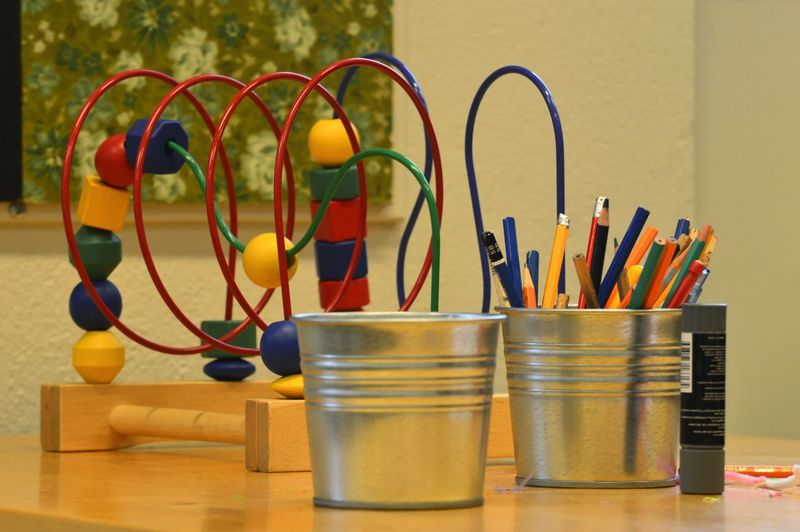 Close-up of multi colored pencils in container by toy on table