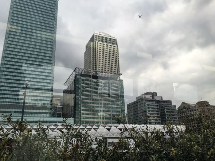 Canary Wharf Docklands Skyscrapers DLR Out Of The Window Train Travel Showcase April London City Airport Flying High Glass And Steel Modern Architecture City Life Reflections Glass Treetops Greenery Leaves Dark Green Shrubbery Grey Sky Dramatic Spot The Difference City Jungle