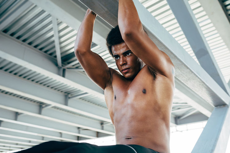 Shirtless Young Hanging From Ceiling While Exercising