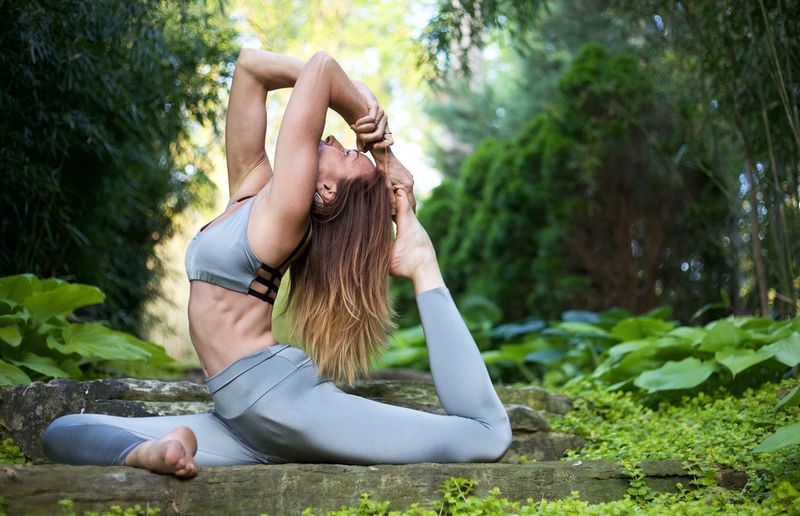 Woman Doing One-Legged King Pigeon Pose Amidst Trees At Forest