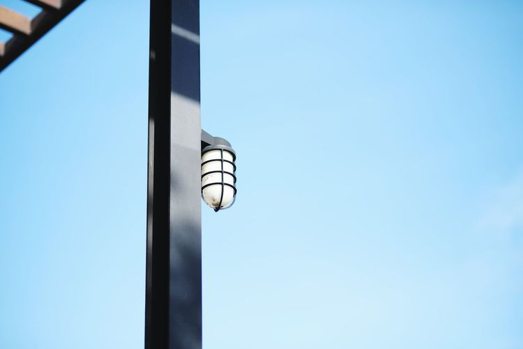 Low angle view of electric lamp against building