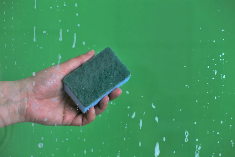 Cropped Hand Cleaning Wet Glass Window With Sponge Against Green Background