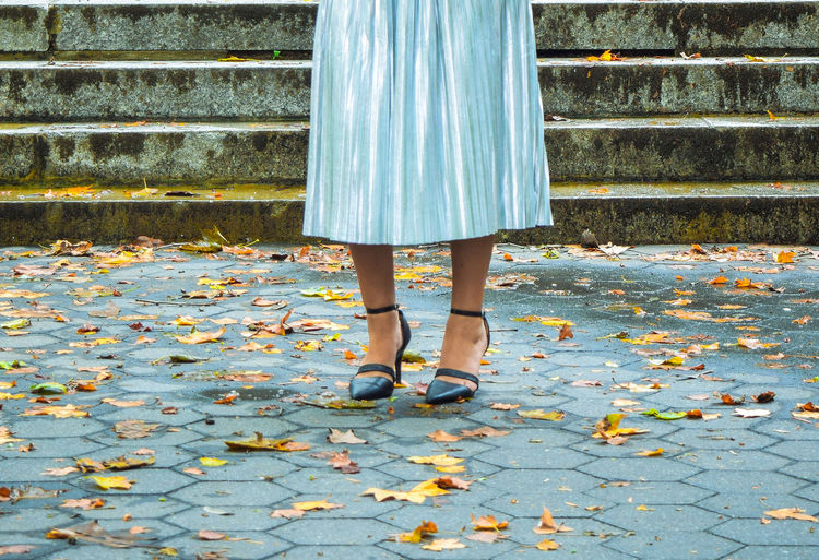 Low section of woman standing by autumn leaves on footpath
