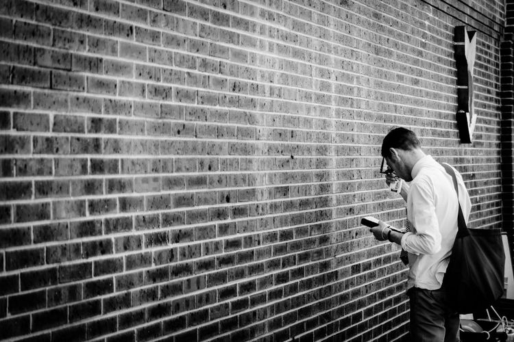 The Wall One Person Looking Down Wireless Technology Brick Wall Technology Holding EyeEmNewHere Real People Standing