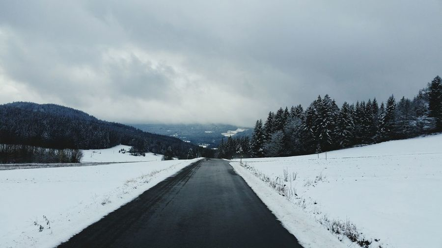Road Amidst Snowy Field Against Cloudy Sky