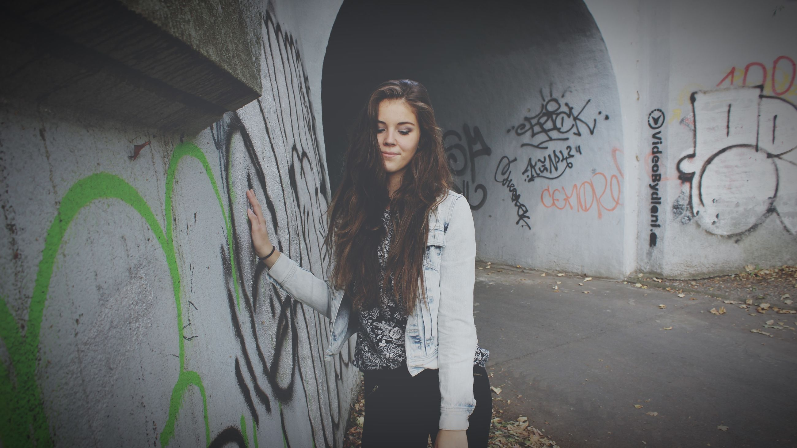 graffiti, wall - building feature, architecture, young adult, built structure, lifestyles, person, art, front view, text, creativity, casual clothing, young women, looking at camera, art and craft, wall, standing, portrait