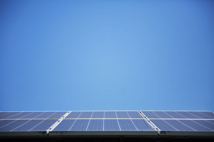 Low angle view of solar panel against blue sky