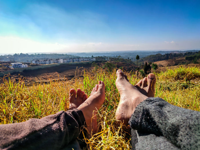 Low section of couple relaxing on field