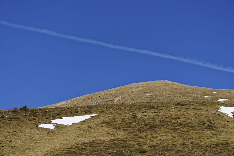 Scenic view of vapor trail against clear blue sky