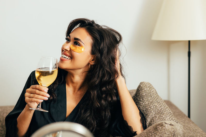 Close-up of woman holding wineglass at home