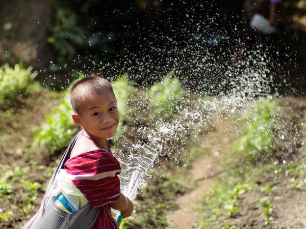 ภาพของนักเรียนที่รดน้ำผักที่ตนได้ปลูกไว้ทาน ที่โรงเรียน ตามโครงการพัฒนาเด็กในถิ่นธุระกันดานขององค์สมเด็จพระเทพฯซึ่งทางโรงเรียนก็ได้ทำต่อเนื่องมาจนถึงทุกวันนี้ In Schools Children Watering Vegetable Plots Children's Skills Good Girl  Happy School Water Watering Vegetables In Schools