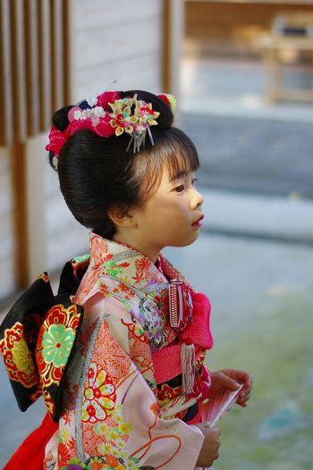 Cute Girl In Traditional Clothing Looking Away While Standing Outdoors