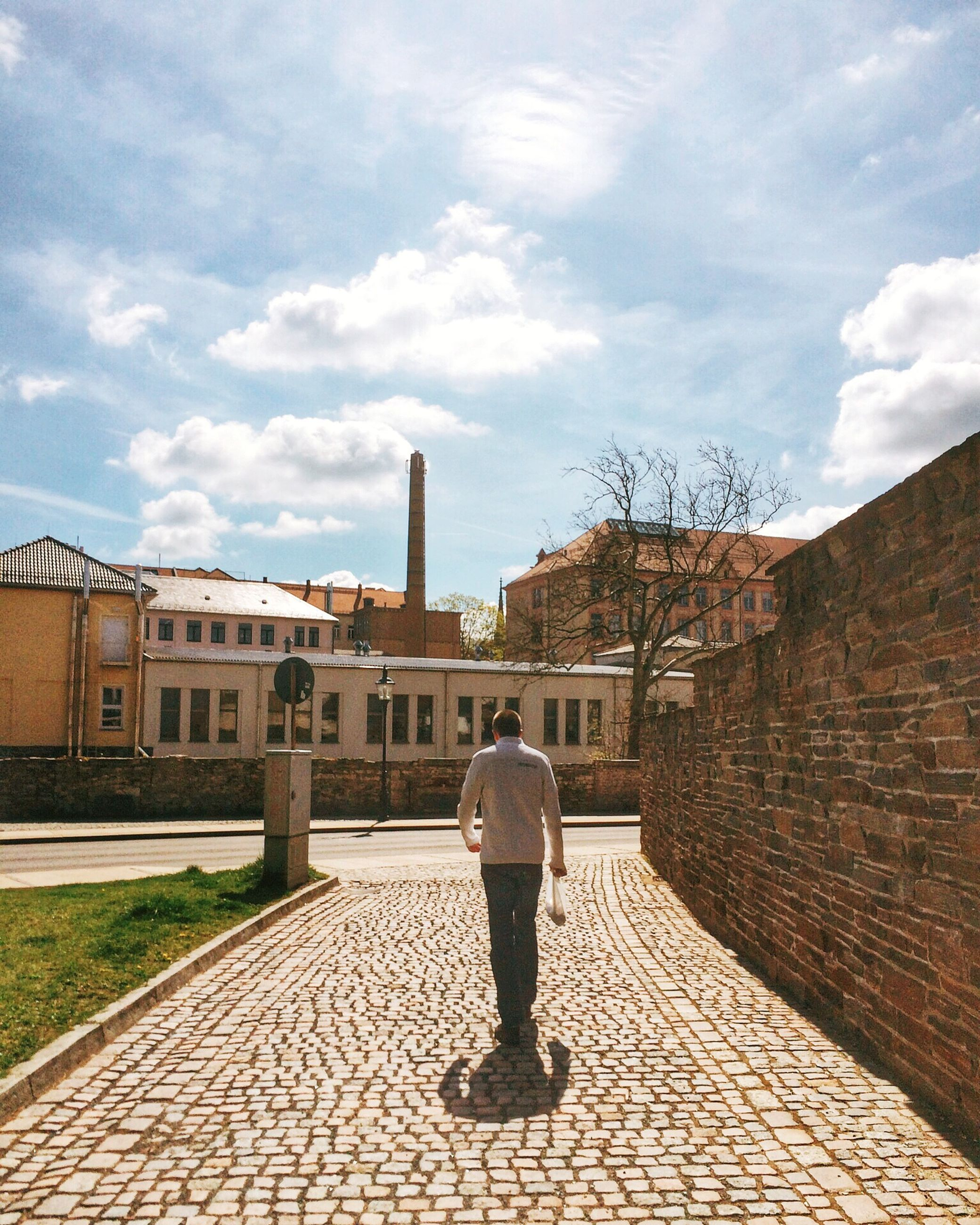 building exterior, architecture, built structure, full length, sky, rear view, lifestyles, casual clothing, leisure activity, cloud - sky, cobblestone, walking, city, standing, street, men, cloud, day