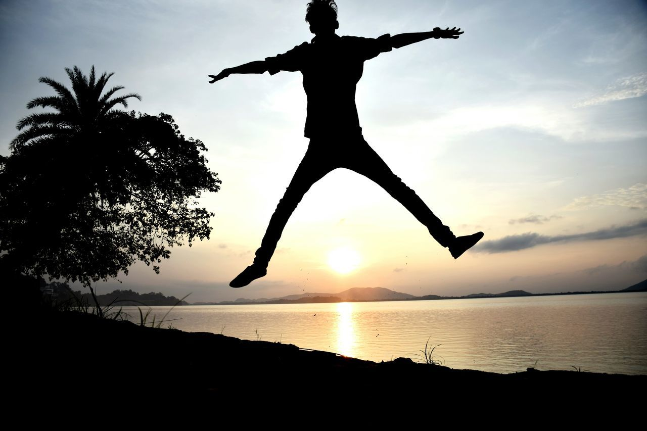 sunset, silhouette, water, orange color, sky, scenics, sea, tranquil scene, tranquility, nature, beauty in nature, jumping, mid-air, beach, sun, tree, outdoors, horizon over water, full length, no people, day