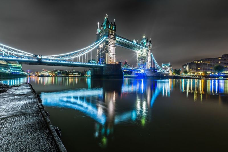 Illuminated tower bridge over thames river in city at night