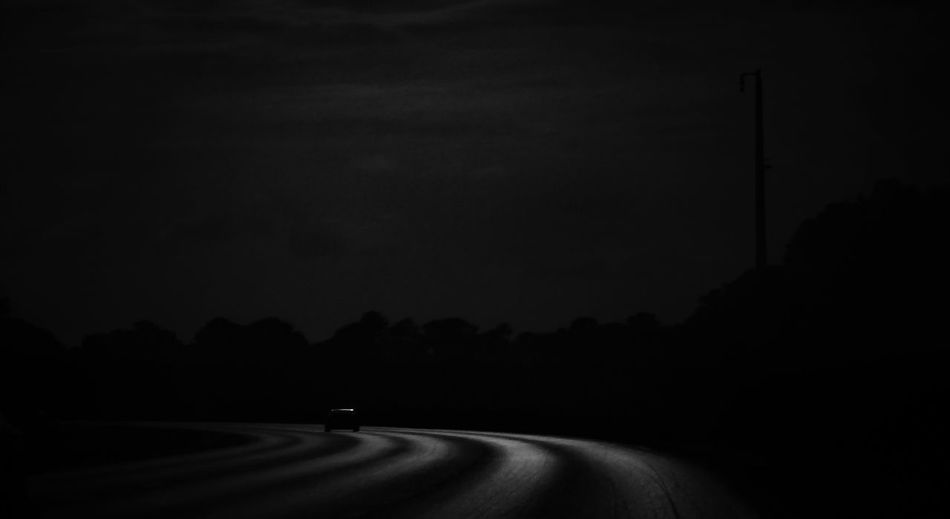 Road amidst silhouette landscape against sky at night