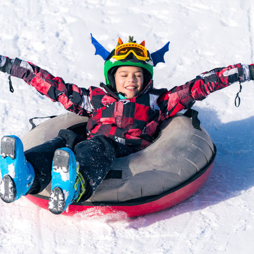 Portrait of happy boy sitting on snow