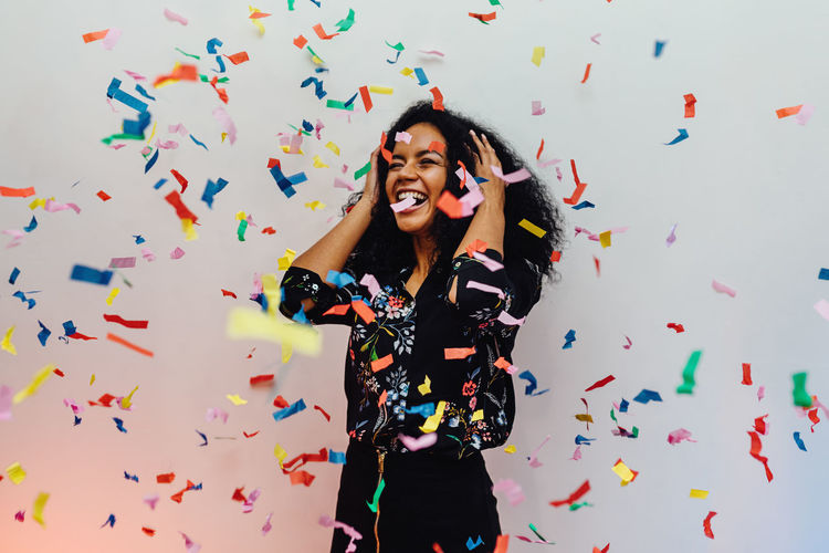 Smiling Young Woman Standing Amidst Confetti Against Wall