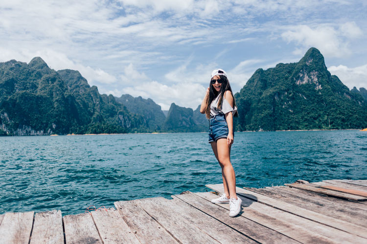Full length of woman standing on sea shore against sky