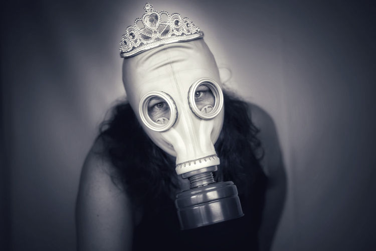 Portrait of woman holding mask against white background
