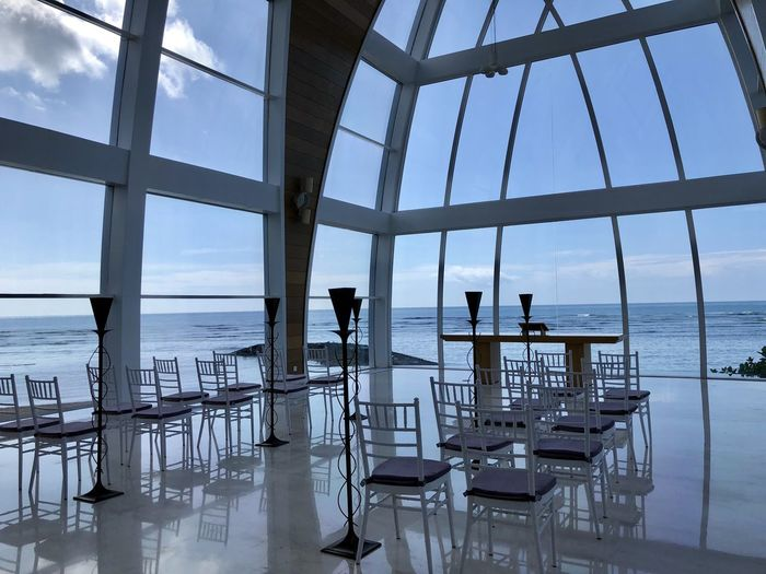 Chairs and table by sea against sky seen through glass window