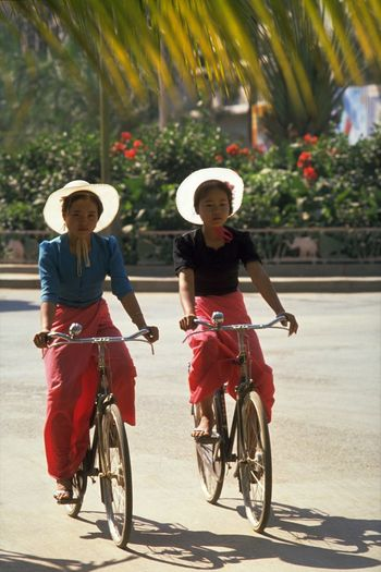 Dai Girl Cyclists in Xishuangbanna. White projects purity, cleanliness, and neutrality. 'Six hours after we left Simao, the muddy Lancangjiang river appeared like a shadow at a lighted window. Another couple of bends and the curtains were flung wide open: Jinghong, the bare lady, lay there on her bed of green'. That's pretty much how I introduce the reader to Xishuangbanna, in Nomadic Gatherings. This area in the deep south of Yunan province, bordering Burma and Laos, is inhabited by a dozen of the minority tribes; namely the Dai, Han, Hanni, Bulang, Lagu, Wa, Yao, Jinuo, Zhuang, Yi, Hui, and Miao. Affected by the monsoon from the Indian Ocean, the region has a climate of high temperature and high rainfall and is mild throughout the year. There are no season distinctions; only wet and dry. The rich forest is said to be roamed by herds of wild elephants, buffaloes, rhinoceroses, tigers, and gibbons. I only had time for a stroll to Chuan Huan Park and the surrounding Dai minority villages. Chickens and pigs roamed freely around the bamboo fenced territories of the raised wooden cottages. The Dai are a colourful and friendly people and the region is celebrated for its annual water-splashing festival in April. I had a tourist meal of shredded pork, fried bananas, and sauteed rice at one of the minority guest house restaurants all for 7 Yuan (60p); and that included the Pi Jiu (beer). http://pics.travelnotes.org/ Authentic Bicycle Calm China Cycling CyclingUnites Cyclists Dai Minorities Enjoy The New Normal Fresh Hats Jinghong Local Michel Guntern People Real People Serene Togetherness Travel Travel Photography Travel Photos Travel Pics Tropical Neighborhood Map Let's Go. Together.