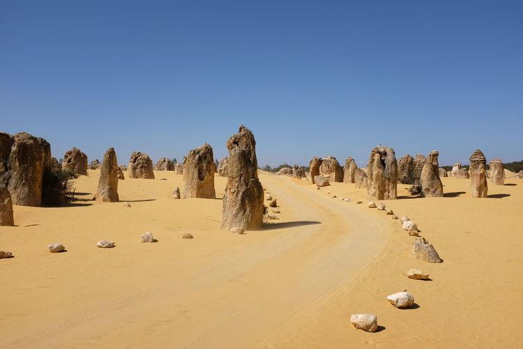 Road amidst pinnacles desert against clear blue sky