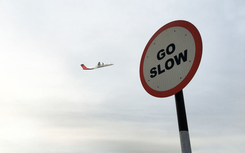 Low angle view of roadsign against airplane