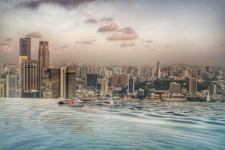 Early morning swim in the sky pool , marina bay sands hotel, overlooking city of singapore