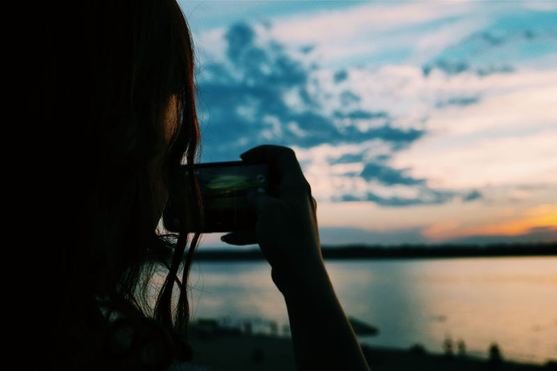 Close-up of woman photographing through smart phone against sky