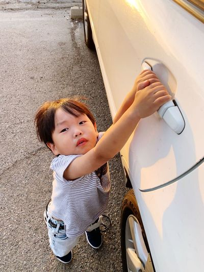 High angle portrait of cute boy holding car handle