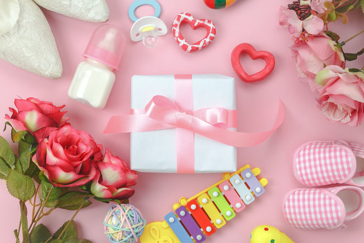 Directly above shot of gift box with baby equipment on pink background