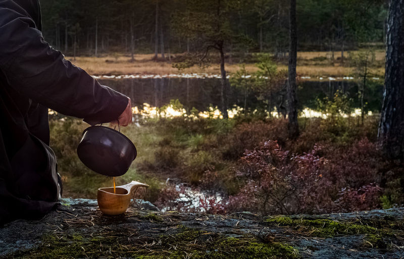Man holding food on field in forest